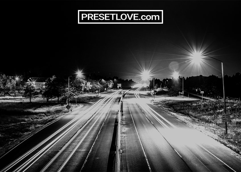 A black and white nighttime photograph of a street