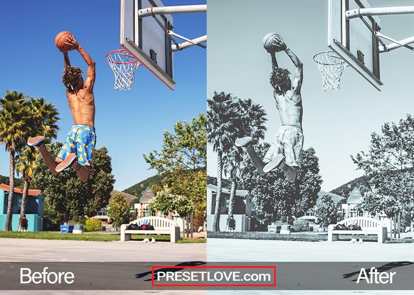 A soft blue monochrome photo of a man dunking a basketball