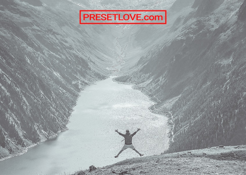 A light monochrome jump shot of a man overlooking a mountain landscape