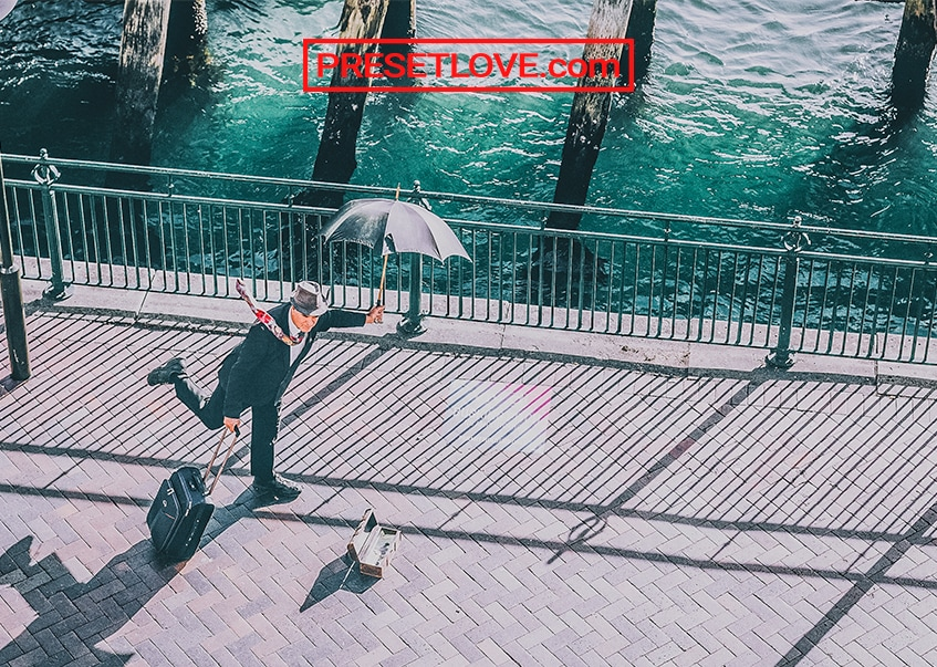 An HDR photo of a man strolling the street in a suit and an umbrella