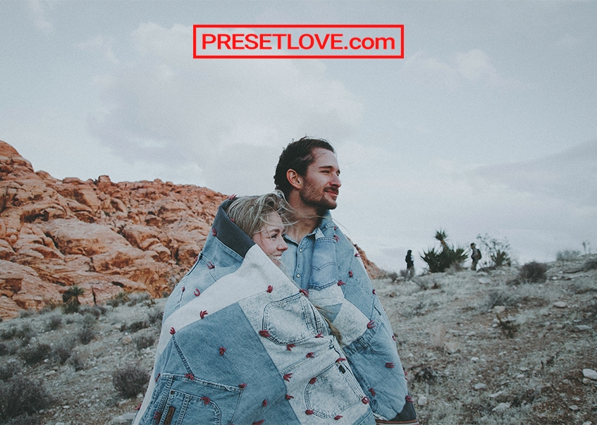 A retro outdoor portrait of a couple wrapped in denim quilt