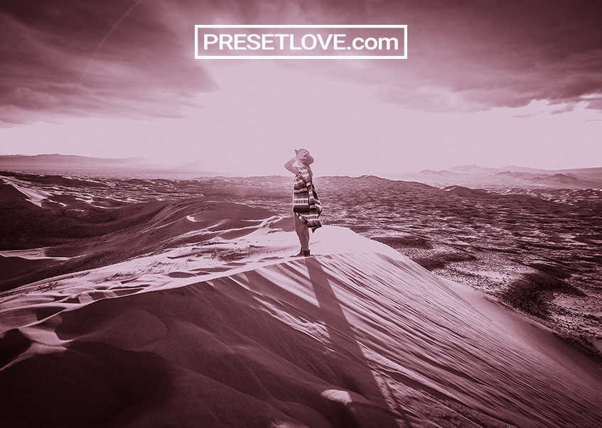 A magenta- tinted photo of a woman in a desert