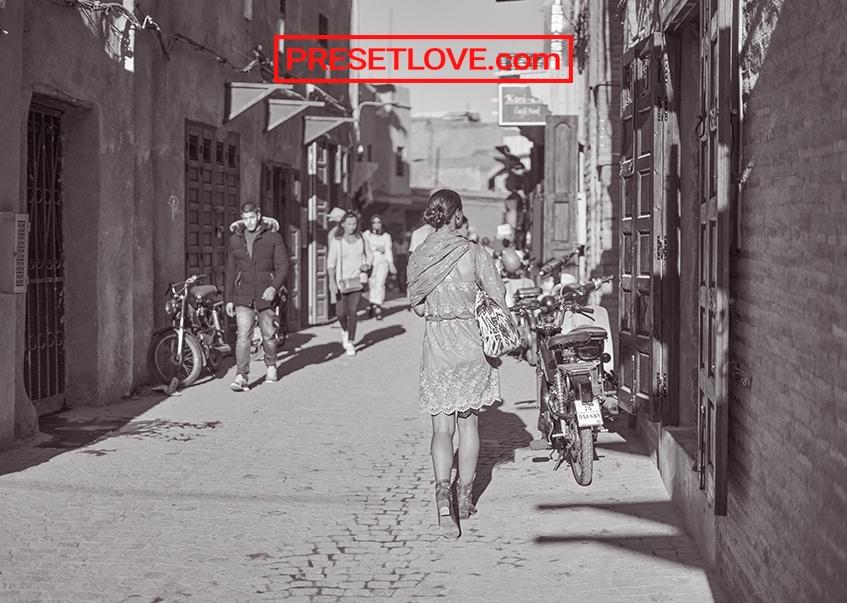 A reddish monochrome photo of an urban street