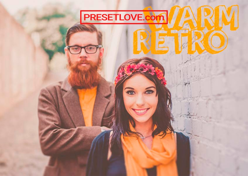 A man and a woman dressed in orange with a hippie vibe