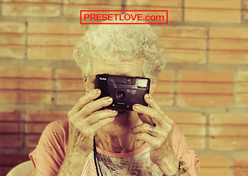 A retro shot of an old lady taking a photo using a film camera