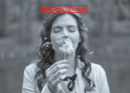 A monochrome photo of a woman smelling a flower