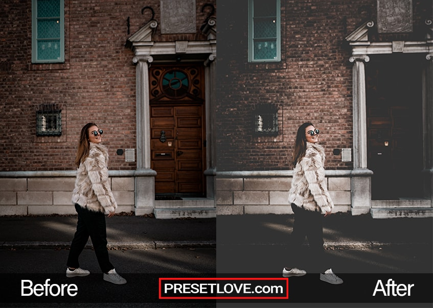 A woman in a thick coat and sunglasses strolling down a street, with a brick structure behind her