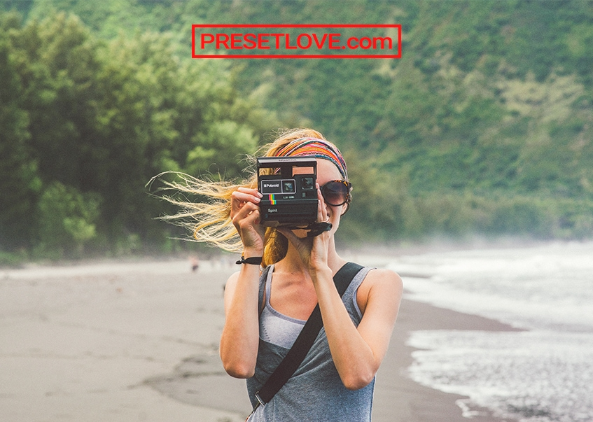 A photo of a woman shooting with a Polaroid outdoors
