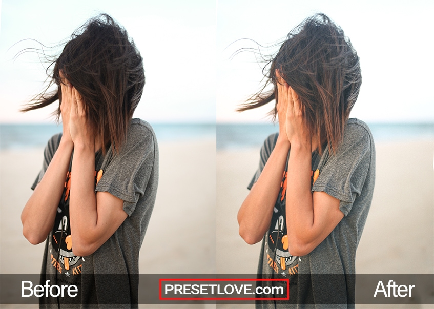 An outdoor photo of a woman with covering her face with her hands