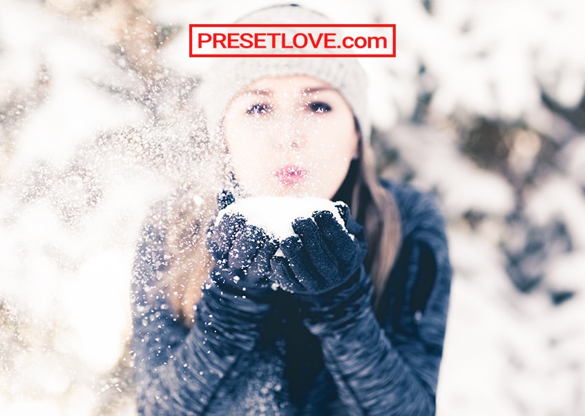 A woman blowing snow to the camera