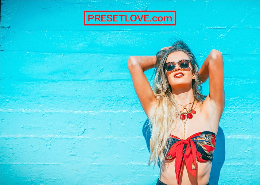 A high-contrast summer portrait of a woman in red bikini against a blue wall