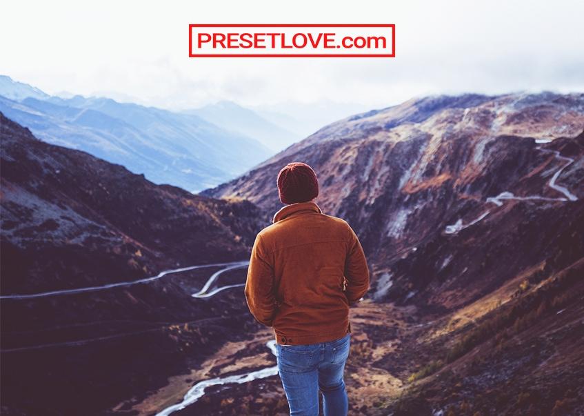 A man facing a vast mountain landscape