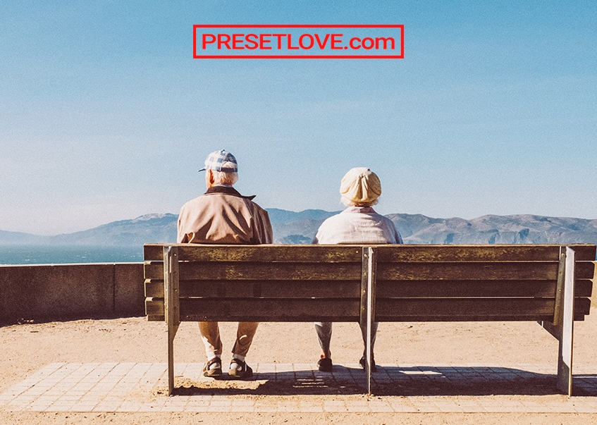 An old couple on a bench facing a landscape
