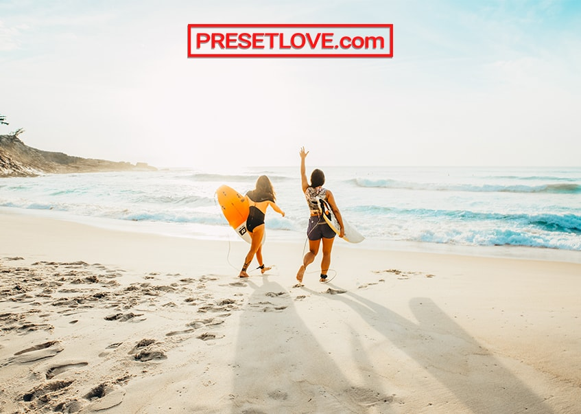 Two women heading towards the sea with their surfboards