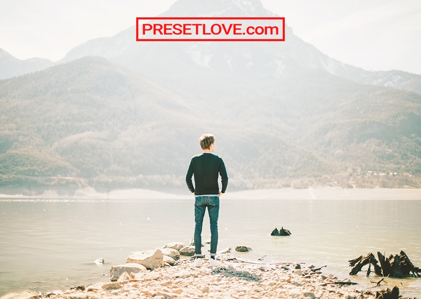 A soft and bright photo of a man standing at a coast