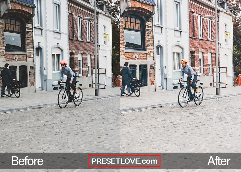 A cool retro photo of a boy riding a bike on a road lined with brick structures