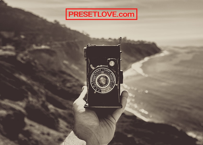 A hand holding up a vintage camera