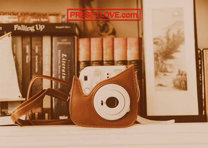 A orange-brown photo of an instant camera on a white desk