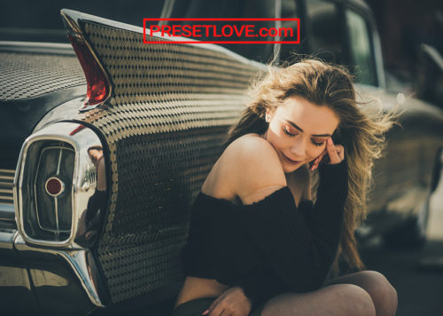 A cinematic photo of a woman sitting down and leaning beside a vintage car