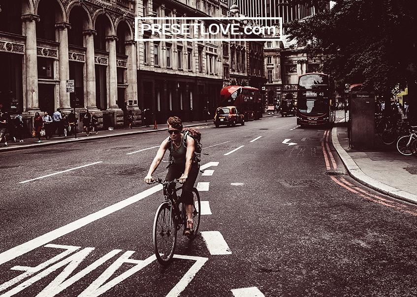 A retro photo of a man biking on a street