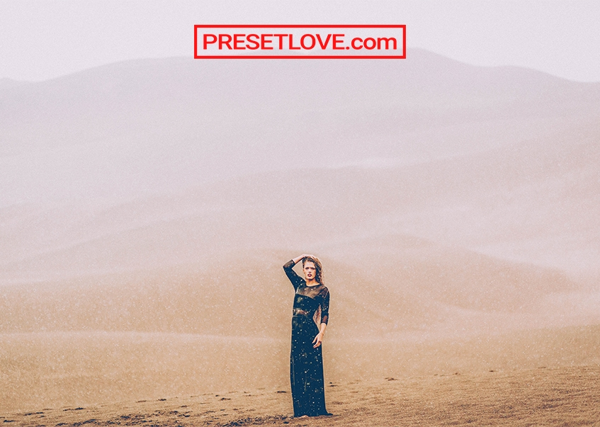 A soft and dramatic photo of a woman in a desert