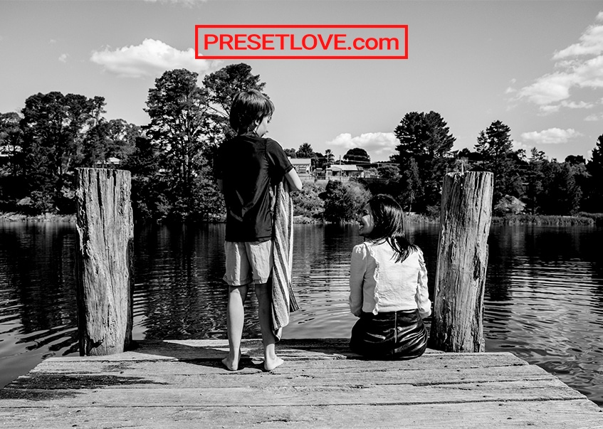 A black and white image of a boy and a woman talking by a river