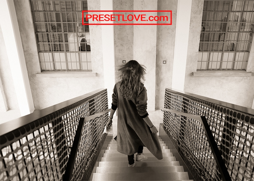 A monochrome film image of a woman walking down the stairs