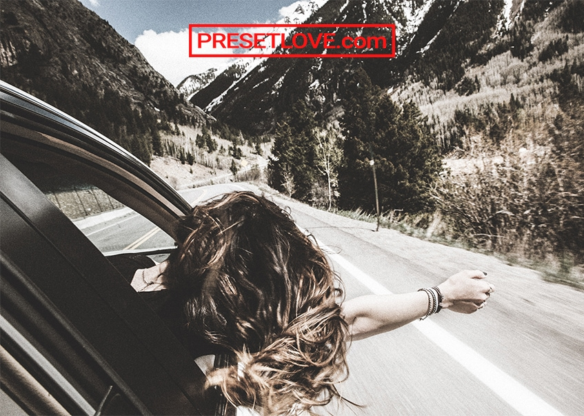 A cinematic image of a woman leaning out the car window with her arm outstretched