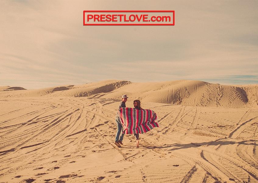 A man and a woman running across a desert