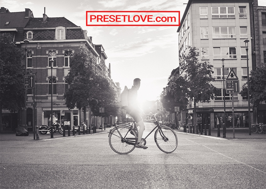 A black and white photo of a man on a bike, in the middle of a street