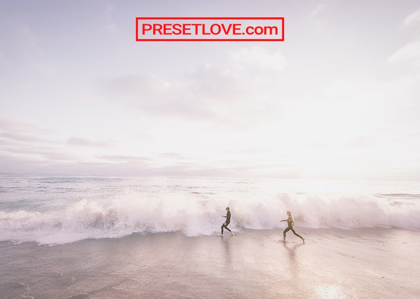 A soft photo of two people running at the beach