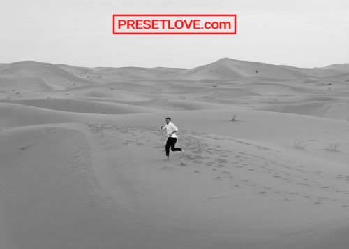 Black and white photo of a man running in a desert