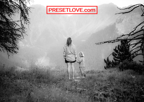 A black and white photo of a mother and child looking out into the landscape