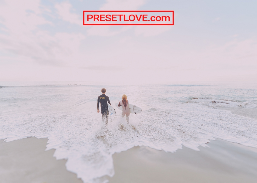 A couple heading to the ocean to surf