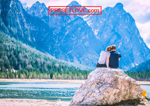A warm photograph of a couple sitting on a rock by the shore