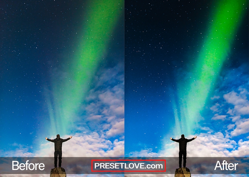 A man standing with outstretched arms in front of an Aurora streak