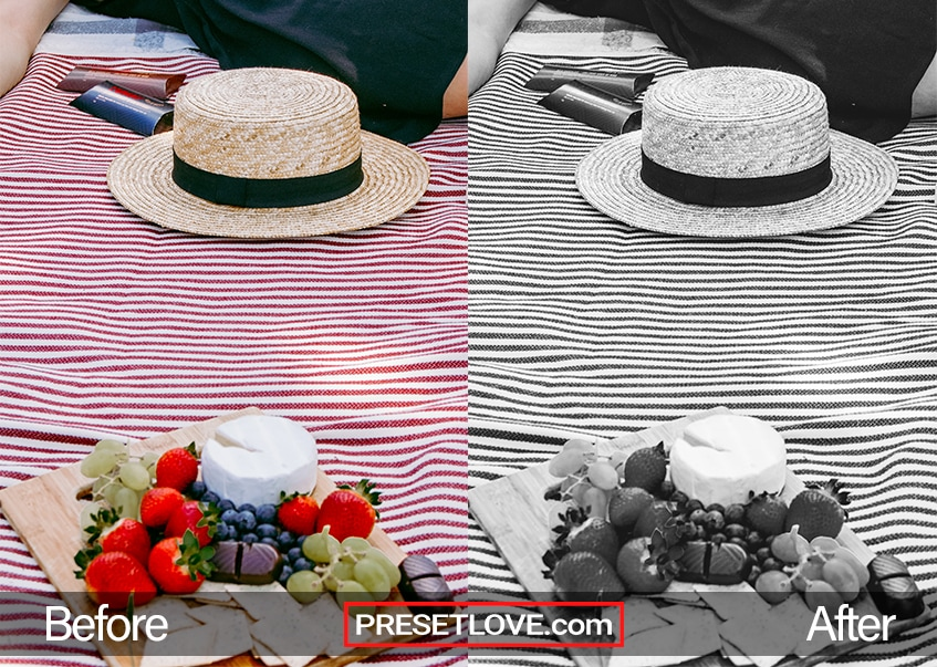 A black and white photo of a hat on top of a striped tablecloth
