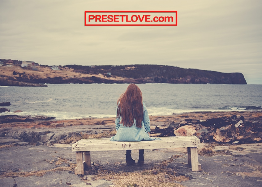 A yellowish photo of a woman sitting on a bench facing the sea