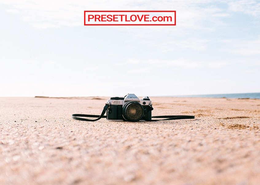 An analog camera on the sand by the beach