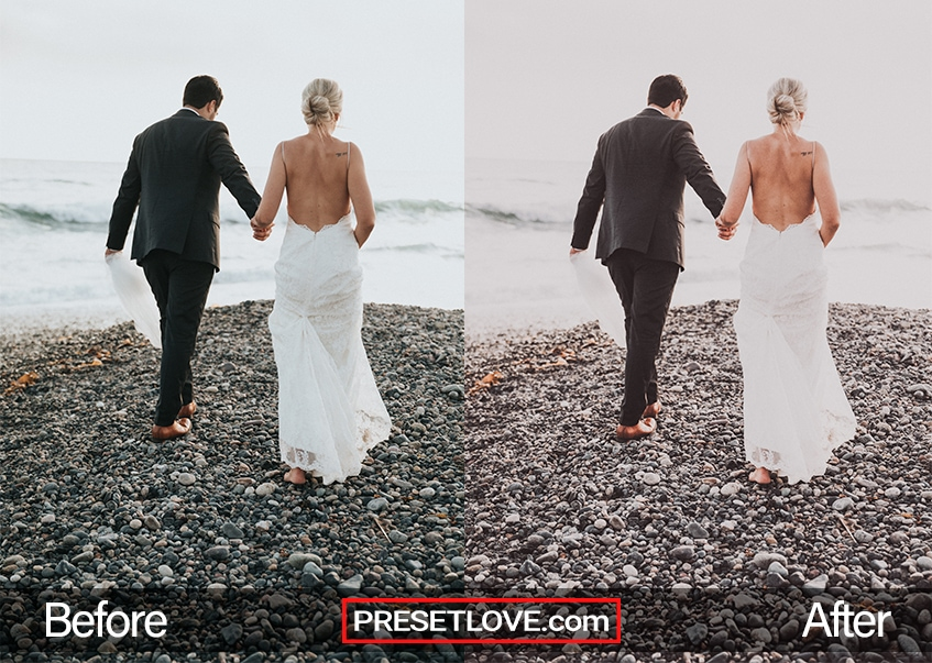 A newlywed couple walking hand-in-hand on a rocky beach