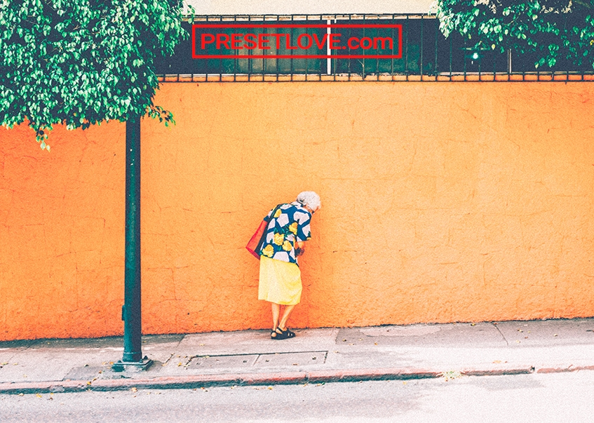 An old lady walking on the sidewalk beside a vibrant yellow wall