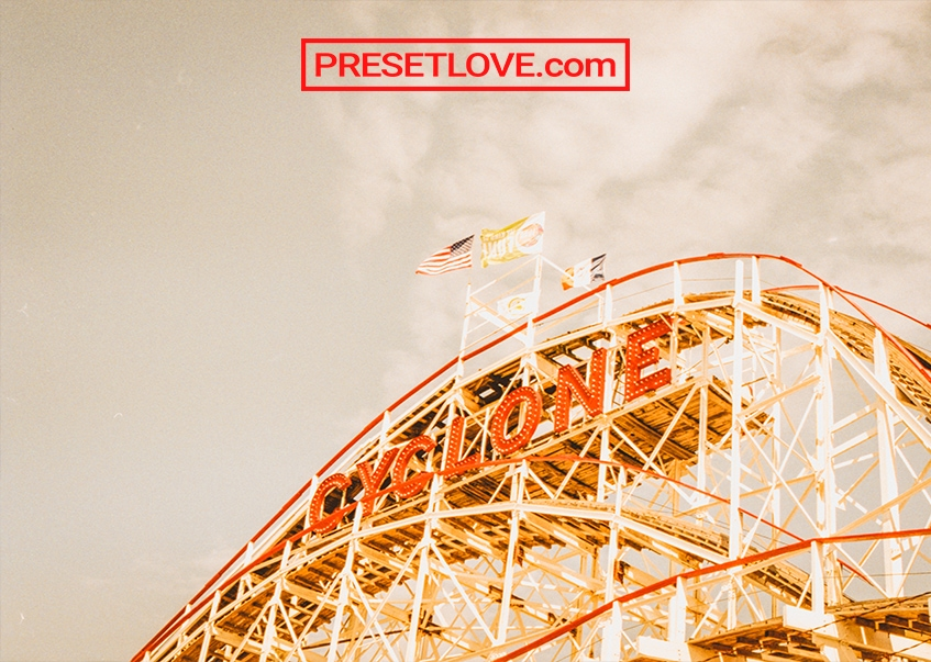A retro photo of a roller coaster with a red sign that says Cyclone