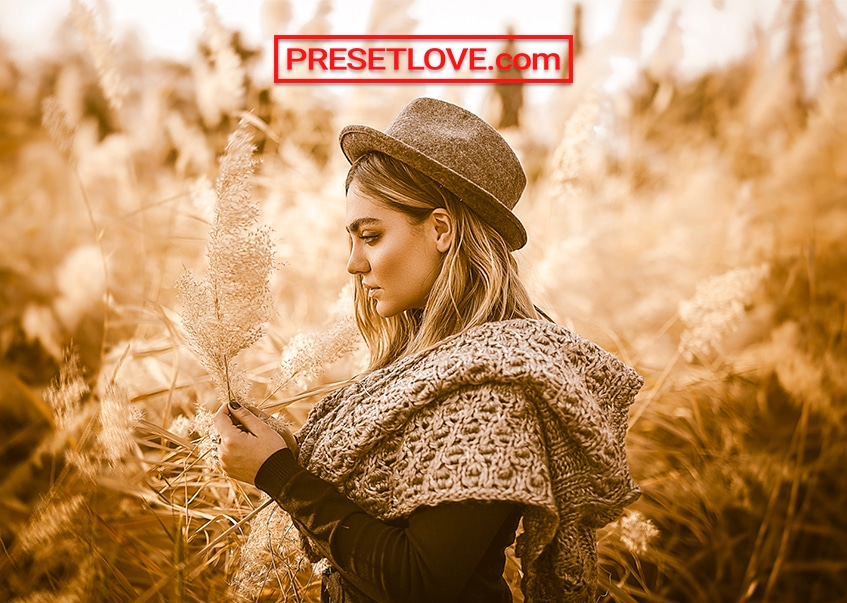 A vivid gold portrait of a woman in a lush field