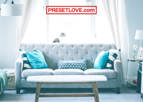 A soft and cool photo of a grey couch with teal pillows