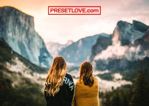 Two women looking towards a breathtaking mountain landscape