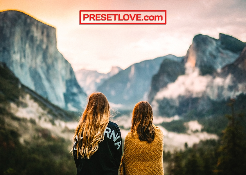 Two women looking towards a breathtaking mountain landscape