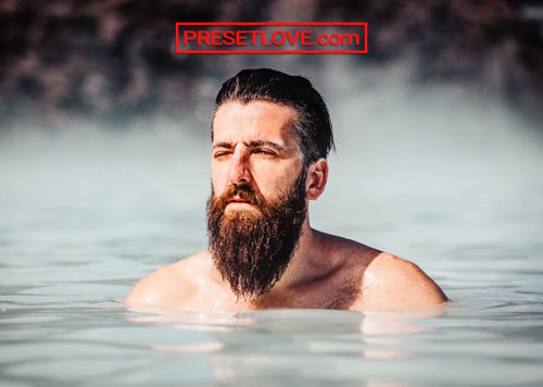 A bearded man in an outdoor spring or pool