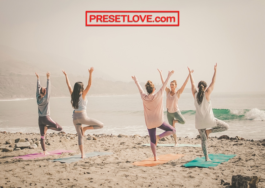 A group of women doing morning yoga at the beach