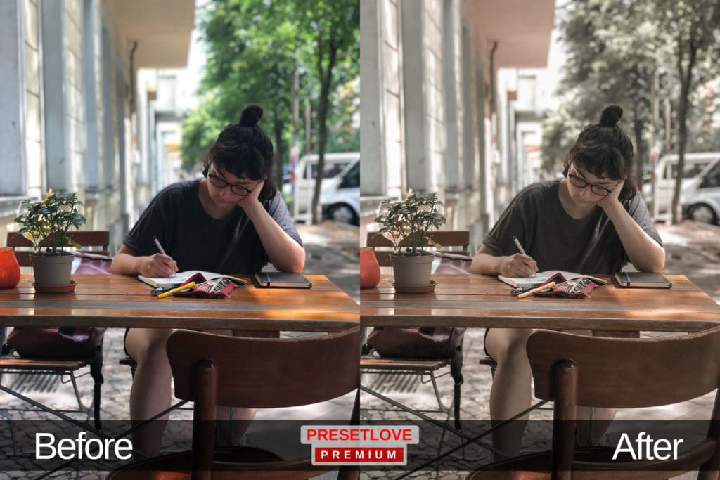 A soft photo of a woman studying at an outdoor wooden cafe table